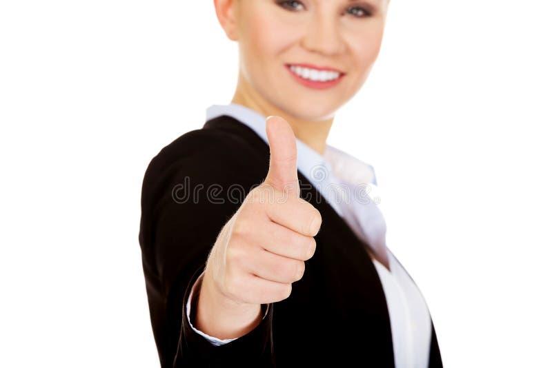 Den unga lyckliga affärskvinnan visar upp tummen arkivbilder