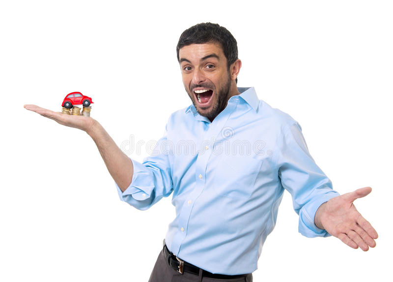 Den unga lyckliga attraktiva mannen med leksakbilen av mynt traver överst isolerat fotografering för bildbyråer