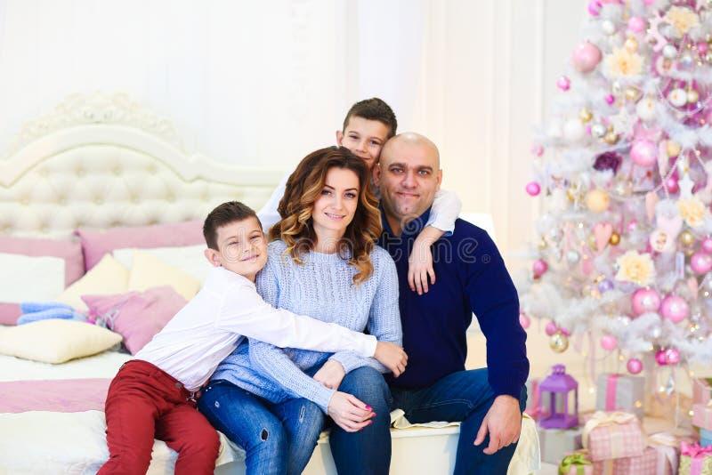 Den unga lyckliga caucasianen uppfostrar sammanträde med söner nära granträd på säng arkivfoton