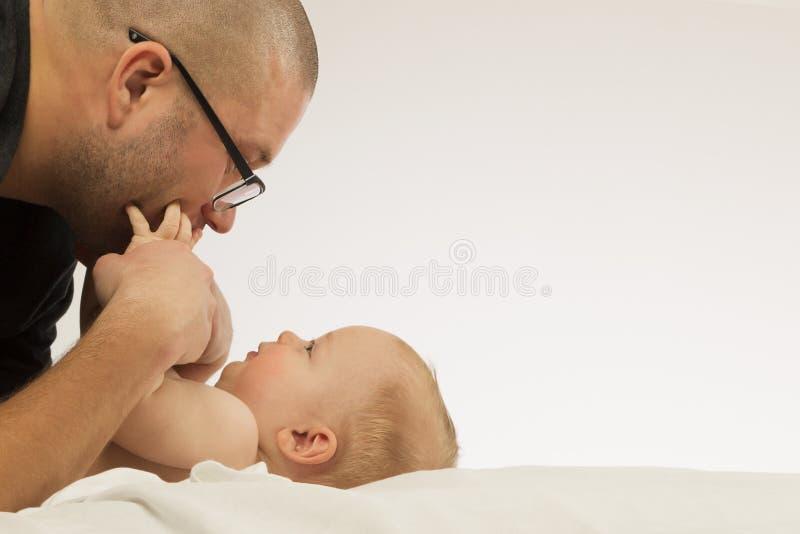 Den unga lyckliga fadern med behandla som ett barn pojkeskytte i fotostudion, att le som poserar på vit bakgrund royaltyfri fotografi