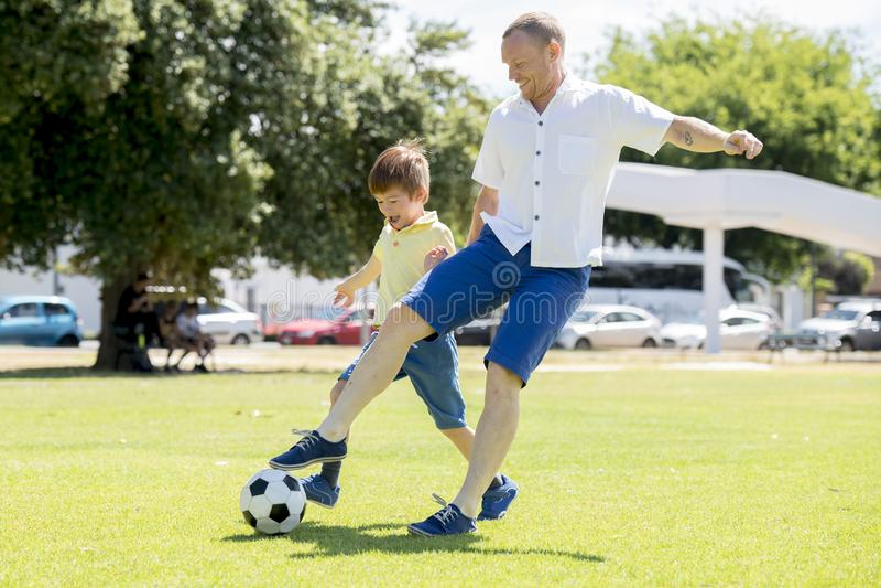 Den unga lyckliga fadern och upphetsade lite 7 eller 8 år gammal son som tillsammans spelar fotbollfotboll på stad, parkerar träd royaltyfria bilder