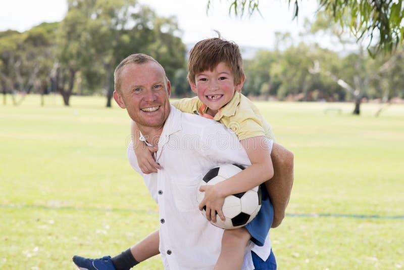 Den unga lyckliga fadern som på bär hans tillbaka upphetsade 7 eller 8 år gammal son som tillsammans spelar fotbollfotboll på sta royaltyfria bilder