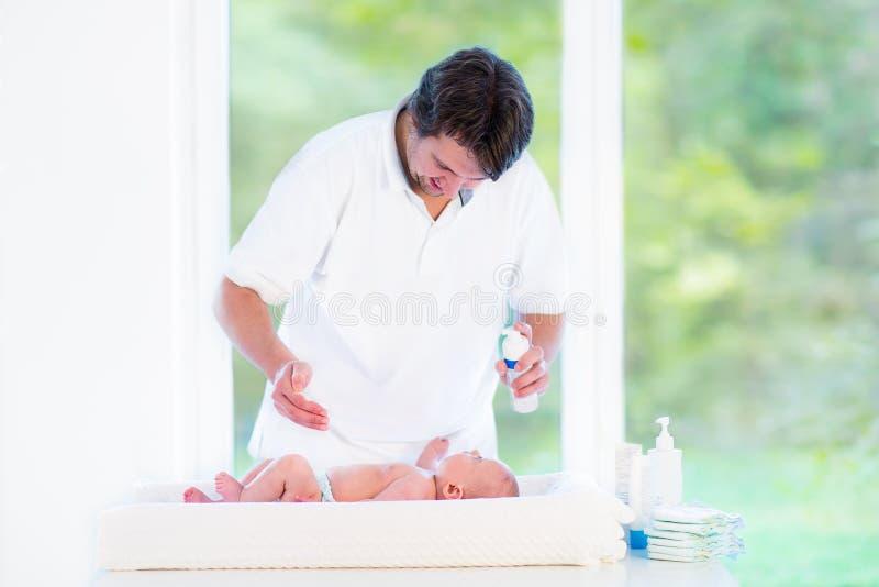 Den unga lyckliga fadern som spelar med hans nyfött, behandla som ett barn sonen arkivfoto