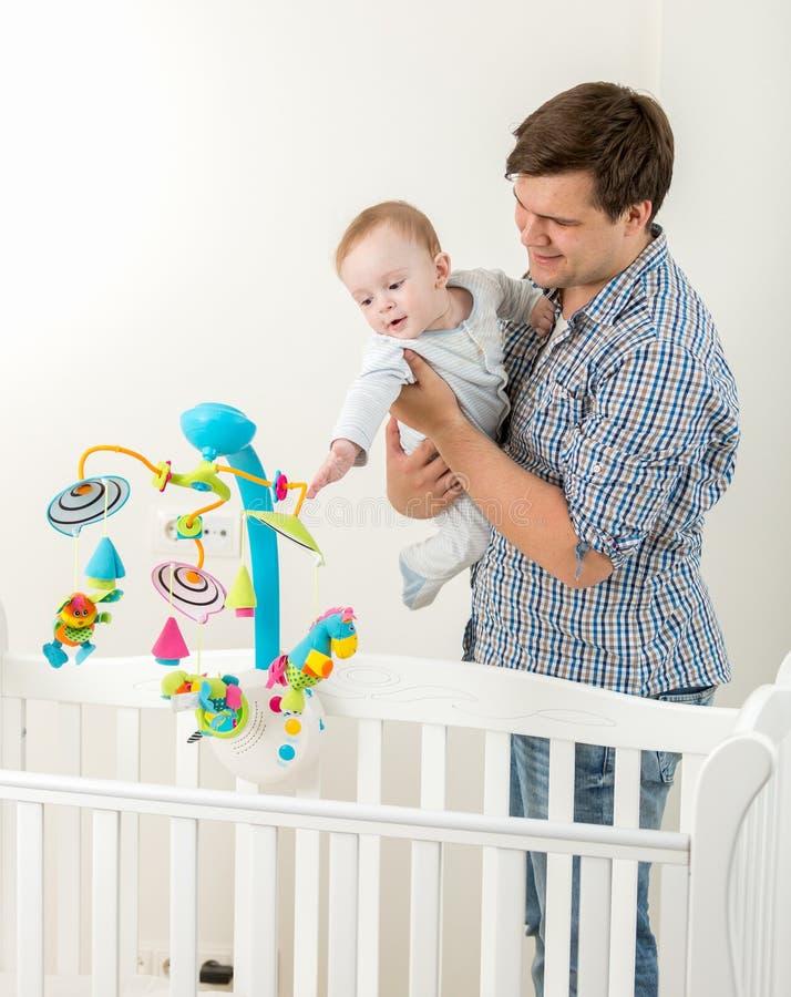 Den unga lyckliga fadern som visar ny leksakkarusell i kåta till hans, behandla som ett barn s royaltyfria foton