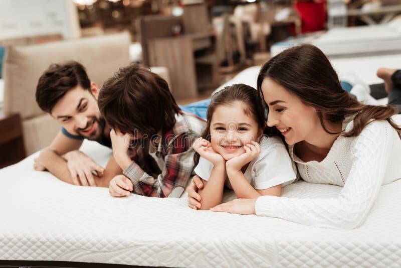Den unga lyckliga familjen kontrollerar på softness av den ortopediska madrassen som ligger på säng i möblemanglager royaltyfri bild