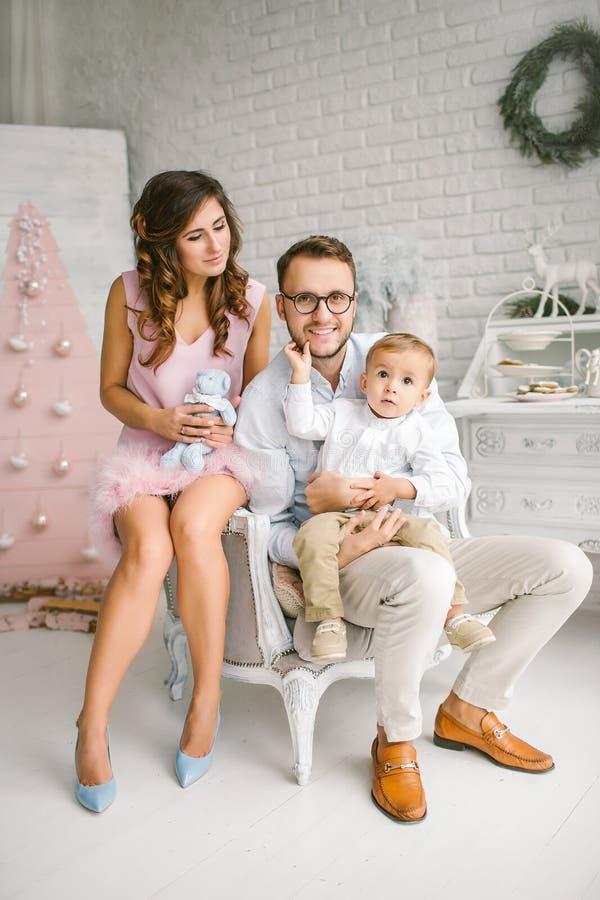 Den unga lyckliga familjen som har gyckel i xmas, dekorerade studion royaltyfria bilder