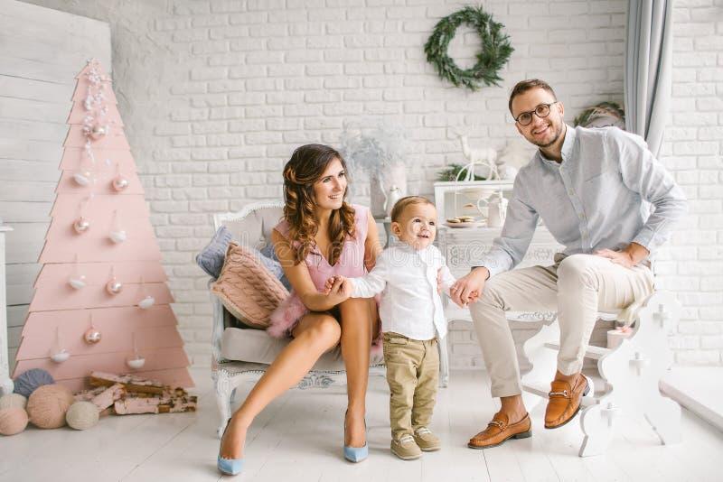 Den unga lyckliga familjen som har gyckel i xmas, dekorerade studion royaltyfri fotografi