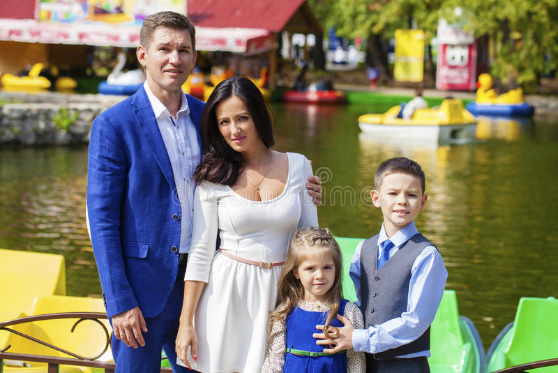 Den unga lyckliga familjståenden på bakgrund av hösten parkerar royaltyfri bild