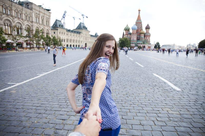 Den unga lyckliga flickan drar grabbhanden på den röda fyrkanten i Moskva arkivbilder