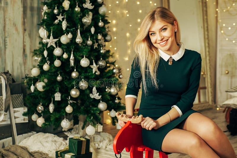 Den unga lyckliga härliga kvinnan med gåvaaskar sitter nära julgranen i rummet av huset arkivfoto