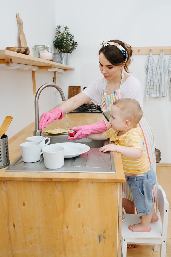 Den unga lyckliga kvinnan i ett kök tvättar hennes sonleksakbil royaltyfri fotografi