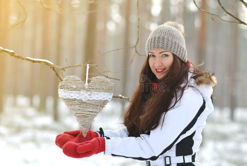Den unga lyckliga kvinnan i vinterjul skrivar ut kläder går i den snöig skogen royaltyfri foto