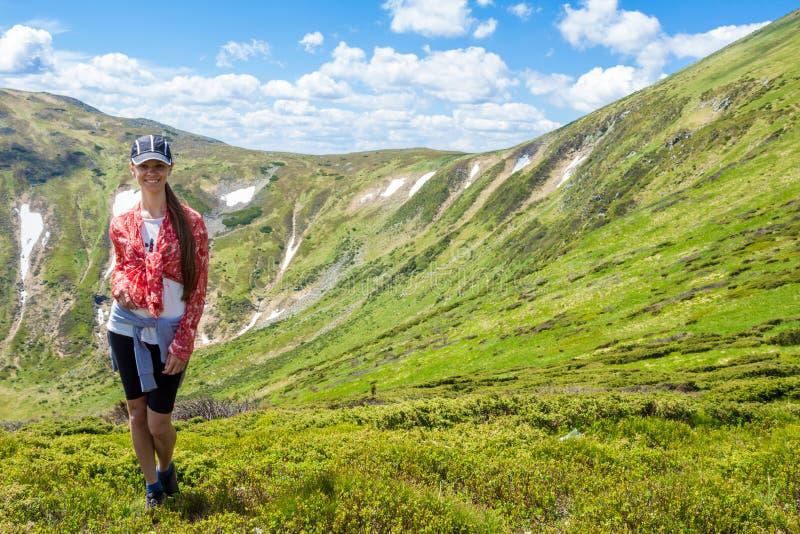 Den unga lyckliga kvinnan på överkanten av kullen tycker om härlig sikt av himmel och berg fotografering för bildbyråer