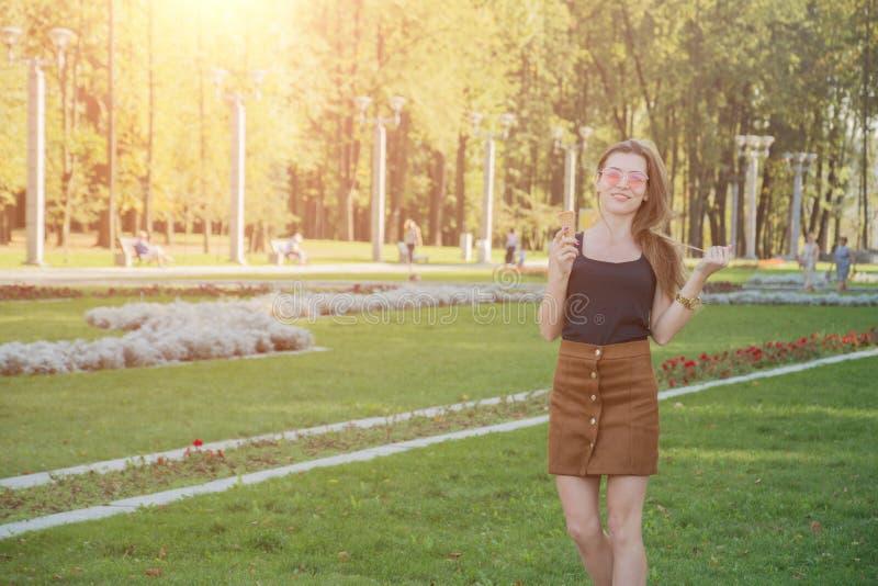 Den unga lyckliga kvinnan parkerar in med glass arkivbilder