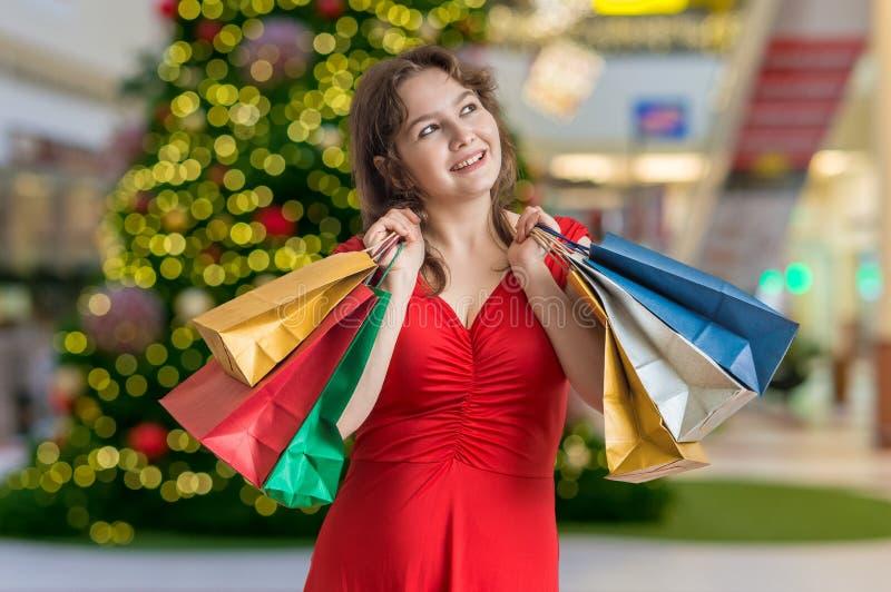 Den unga lyckliga kvinnan shoppar gåvor för jul fotografering för bildbyråer