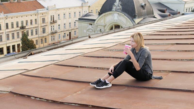 Den unga lyckliga kvinnan sitter med kaffe på taket Vind som blåser hennes hår royaltyfri bild
