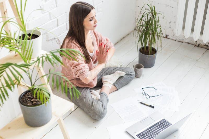 Den unga lyckliga kvinnan sitter p? golvet i en yoga poserar i en ljus l?genhet och arbetar bak en b?rbar dator, en freelancerfli royaltyfri foto