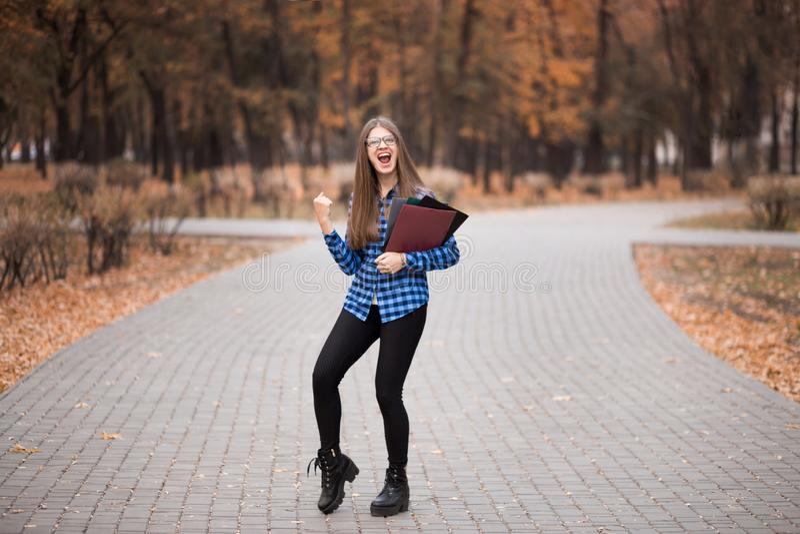 Den unga lyckliga kvinnan som gör en gest seger med den lyftta näven, kvinna passerade examina royaltyfria foton