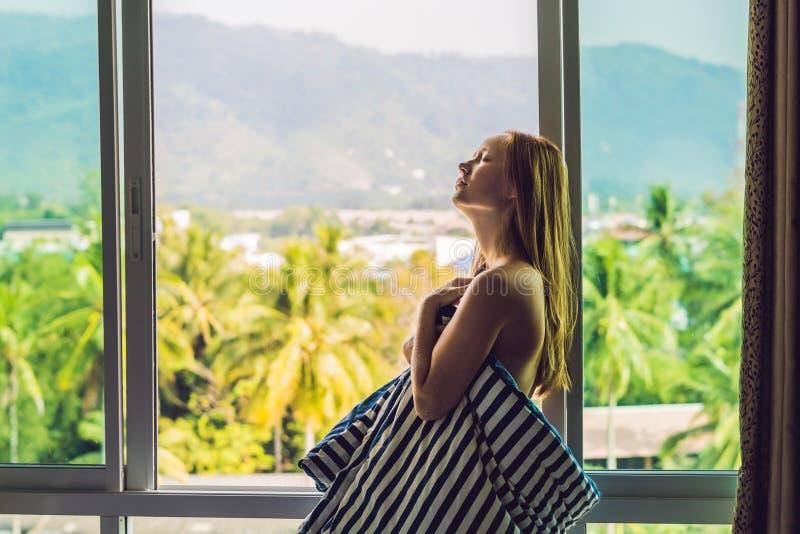 Den unga lyckliga kvinnan vaknade upp i morgonen i sovrummet vid fönstret med härliga bergsikter arkivbild