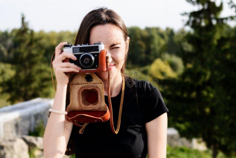 Den unga lyckliga kvinnliga fotografen går i parkera med den retro kameran royaltyfri fotografi