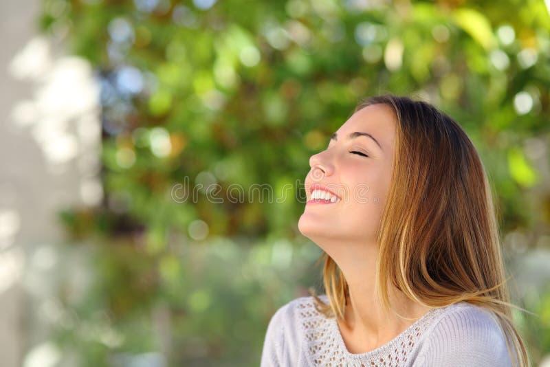 Den unga lyckliga le kvinnan som gör djup andedräkt, övar arkivfoton