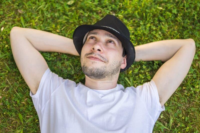 Den unga lyckliga mannen är ligga, och avslappnande i gräs parkera in och att tänka eller att drömma arkivfoton