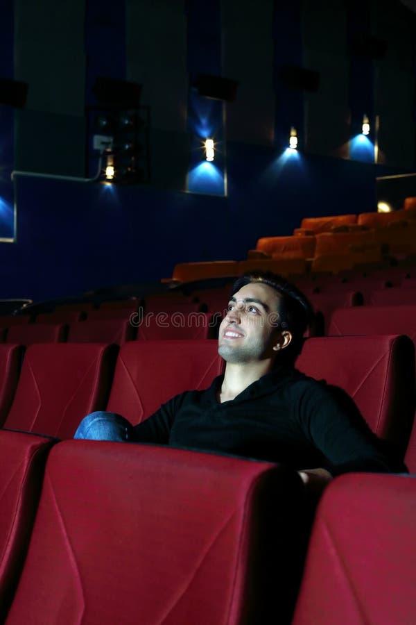 Den unga lyckliga mannen håller ögonen på film och vilar i bioteater arkivbild