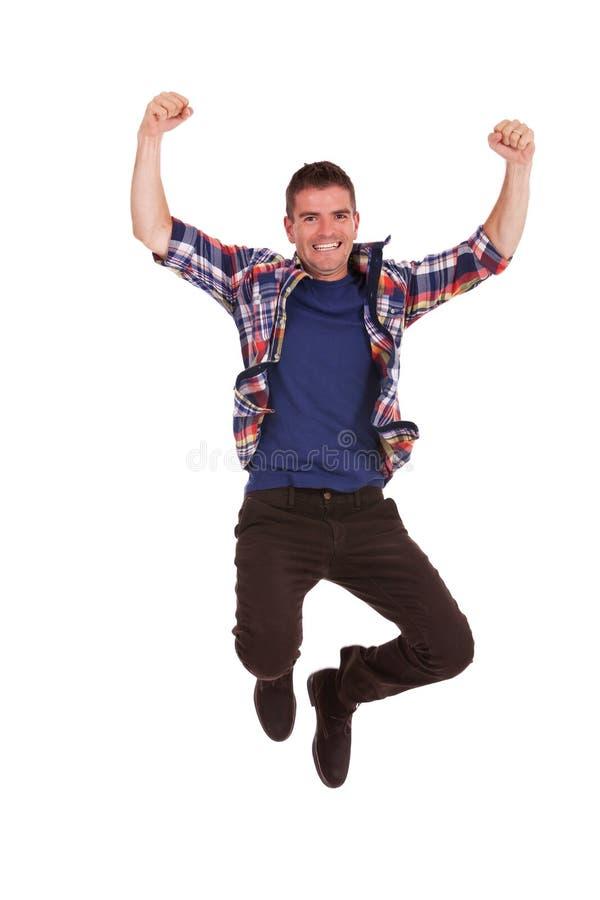 Den unga lyckliga mannen hoppar i luft arkivbild