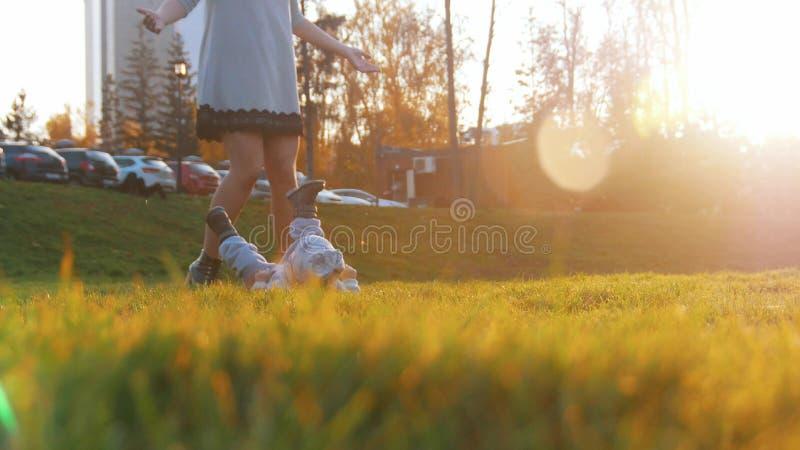 Den unga lyckliga modern och hennes lite att behandla som ett barn pojken som in spelar, parkerar Behandla som ett barn att ligga royaltyfri fotografi