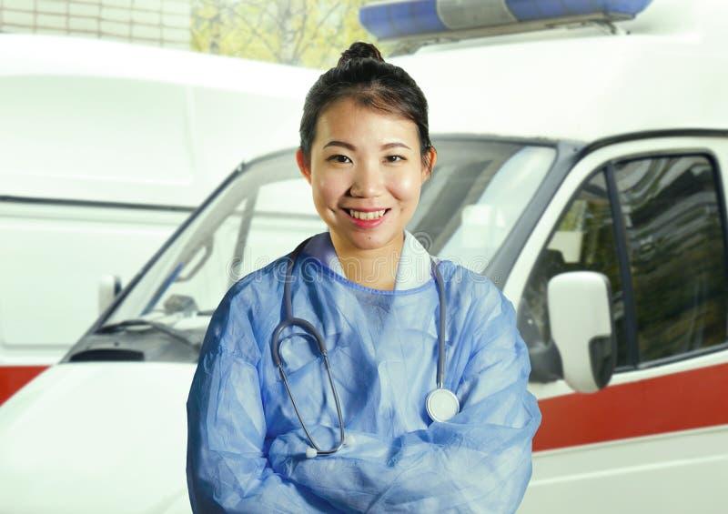 Den unga lyckliga och attraktiva asiatiska koreanska medicindoktorskvinnan i blått skurar att le gladlynt det fria framme av nödl arkivbilder