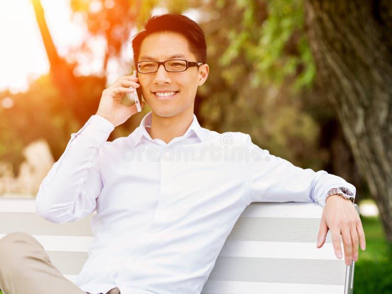 Den unga lyckliga och lyckade affärsmannen under hans avbrott parkerar in royaltyfri bild