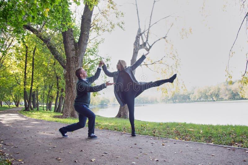 Den unga lyckliga pardansen i hösten parkerar Solig dag guld- höst royaltyfria foton