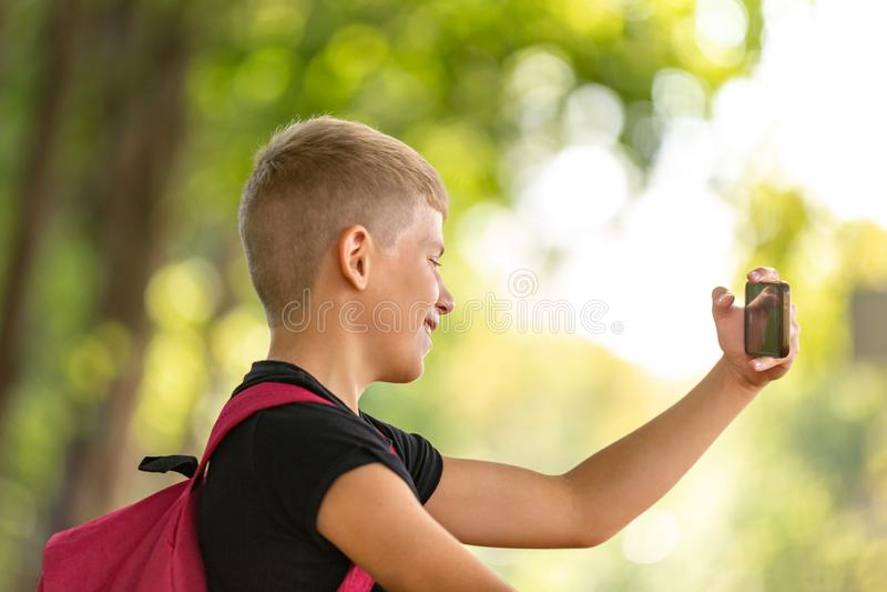 Den unga lyckliga preteen pojken som går i varm solig sommardag i, parkerar och tar selfie på smartpone royaltyfri fotografi