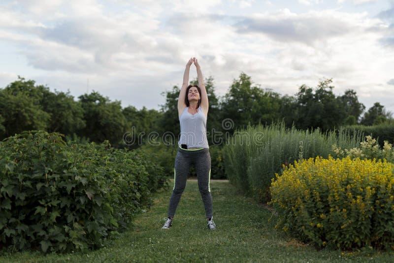 Den unga lyckliga sportiga kvinnan som sträcker efter jogga övning i staden, parkerar royaltyfri foto