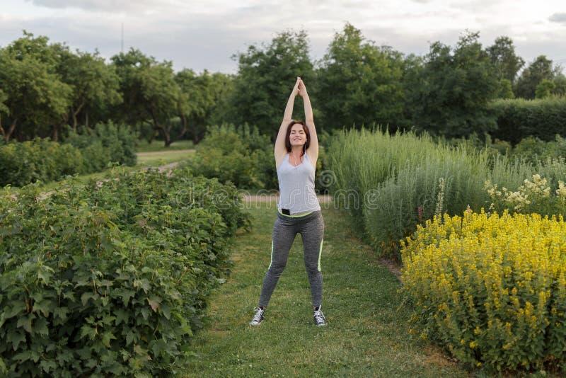 Den unga lyckliga sportiga kvinnan som sträcker efter jogga övning i staden, parkerar arkivbild