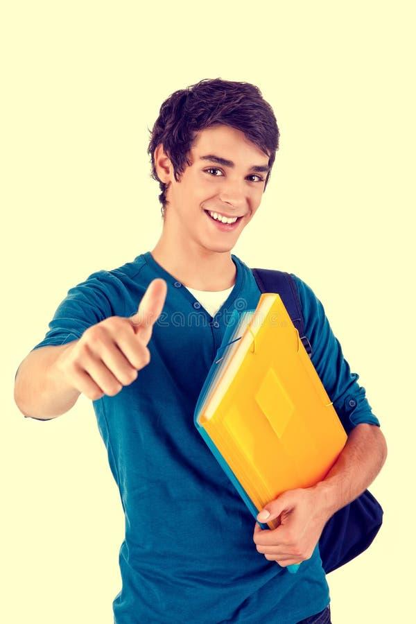 Den unga lyckliga studentvisningen tummar upp royaltyfri foto