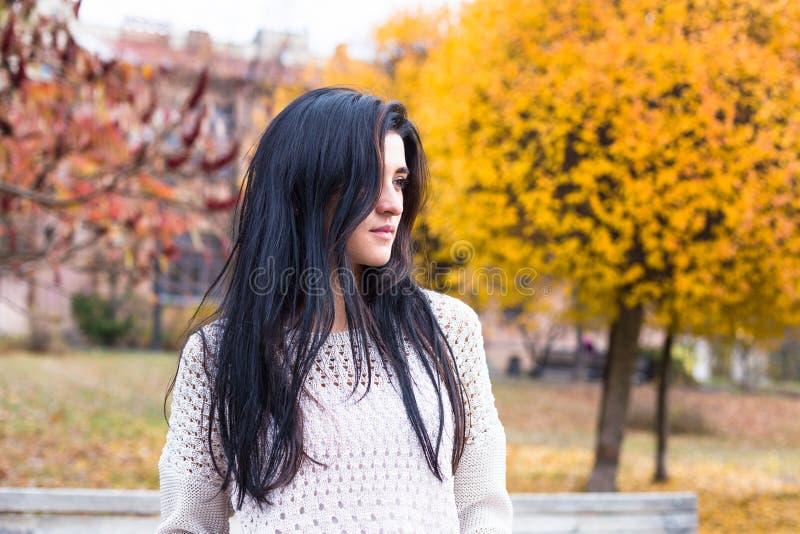 Den unga lyckliga tonårs- flickan som har gyckel i höststad, parkerar royaltyfri foto