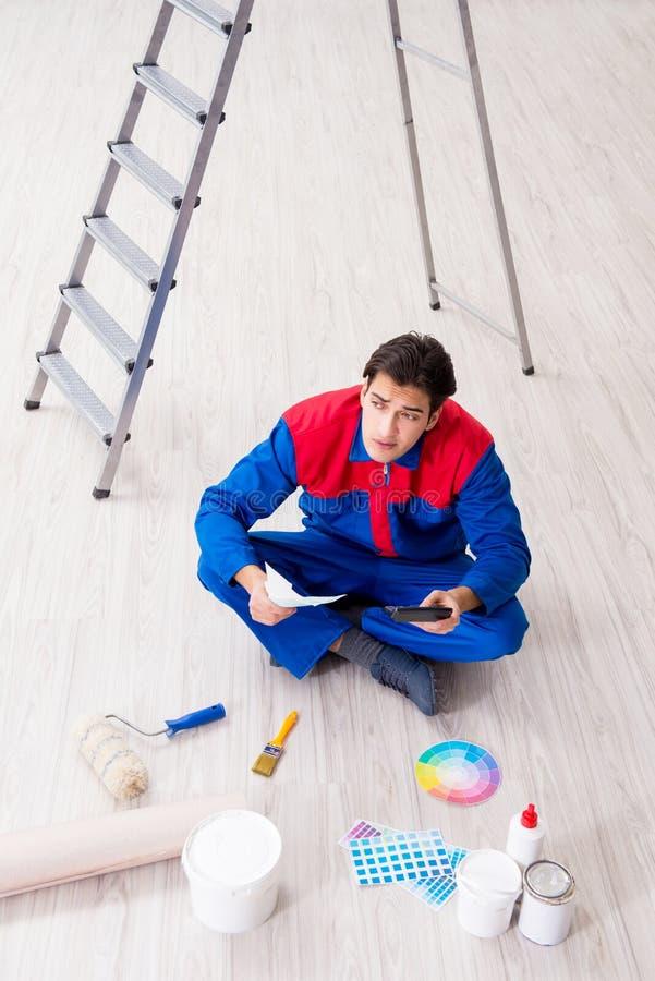 Den unga målaren som försöker att matcha färger för att måla jobb fotografering för bildbyråer