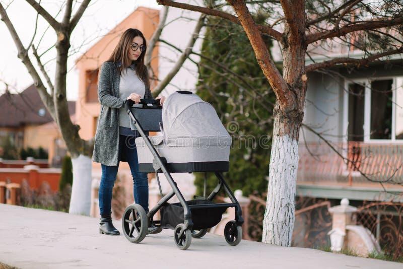 Den unga mamman som går med sittvagnen i, parkerar Den stilfulla modern med behandla som ett barn royaltyfri foto