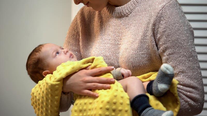 Den unga mamman som rymmer förtjusande nyfött, behandla som ett barn, i armar och att beundra honom, förälskelse fotografering för bildbyråer