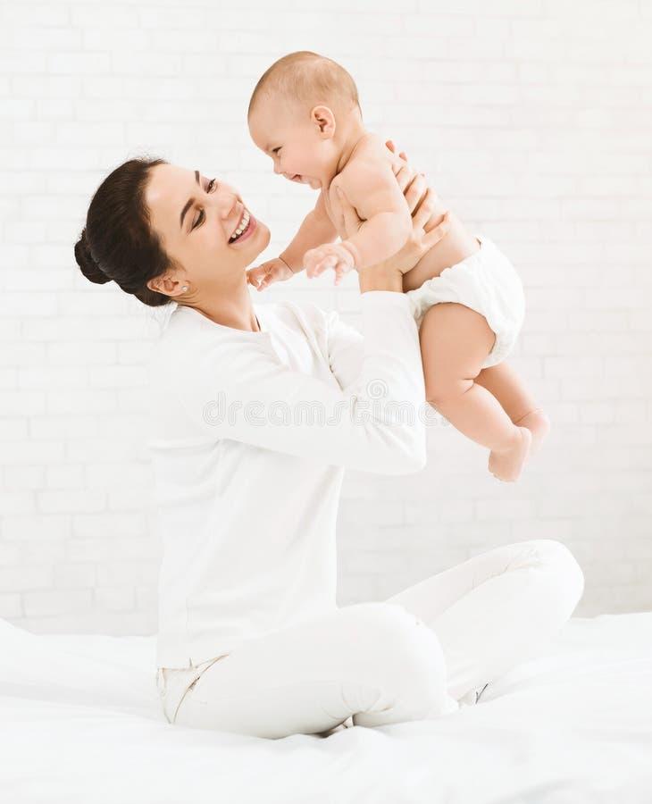 Den unga mamman som rymmer hennes lyckligt, behandla som ett barn i luft arkivbilder