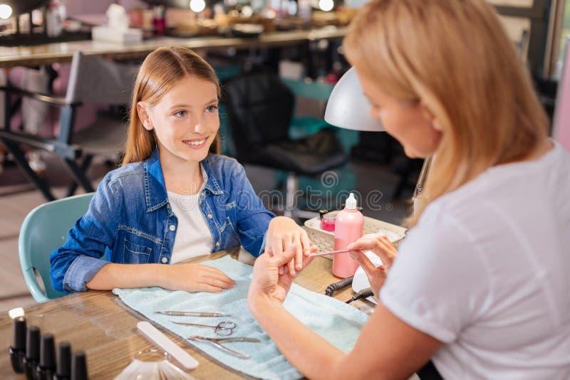 Den unga manikyristarkiveringslillfingret spikar av en tonårs- flicka royaltyfri foto