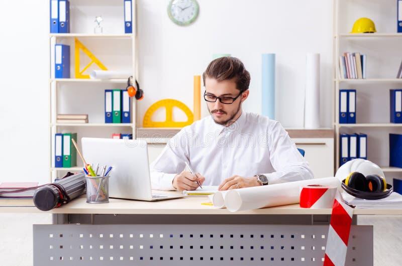 Den unga manliga arkitekten som arbetar i kontoret royaltyfria bilder