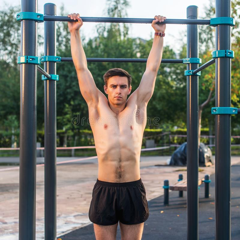 Den unga manliga idrottsman nen som gör hakan-upp, övar i parkera Konditionman som utanför utarbetar royaltyfri bild
