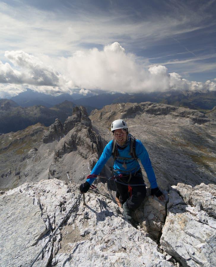 Den unga manliga klättraren når toppmötet, når han har gjort a via Ferrata i de italienska dolomitesna arkivbilder