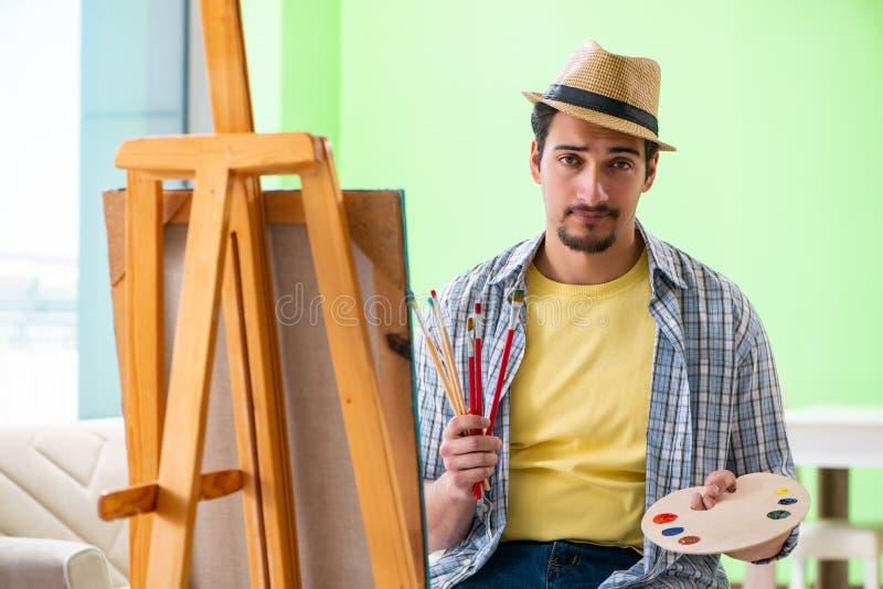 Den unga manliga konstnären som arbetar på ny målning i hans studio royaltyfri foto