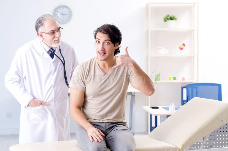Den unga manliga patienten som bes?ker den gamla doktorn royaltyfri foto