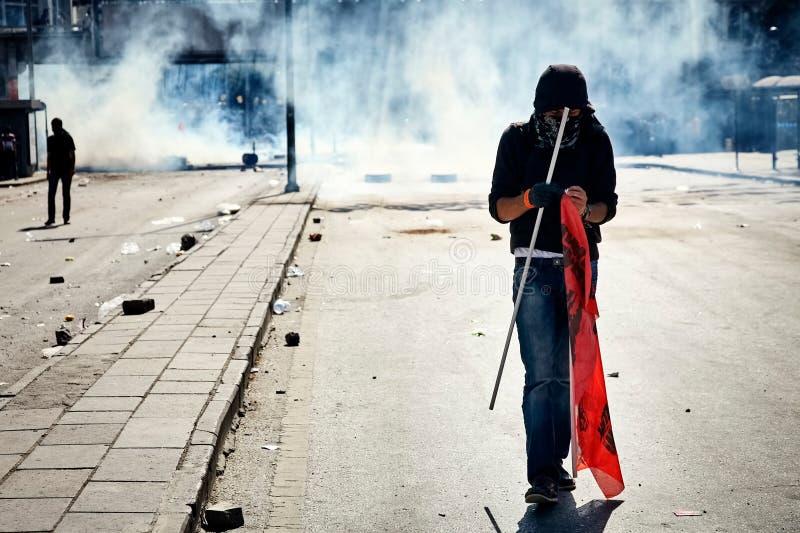 Den unga manliga personen som protesterar som rymmer en flagga, går på gatan som täckas av tårgas som avfyras av polisen under Ge royaltyfri foto