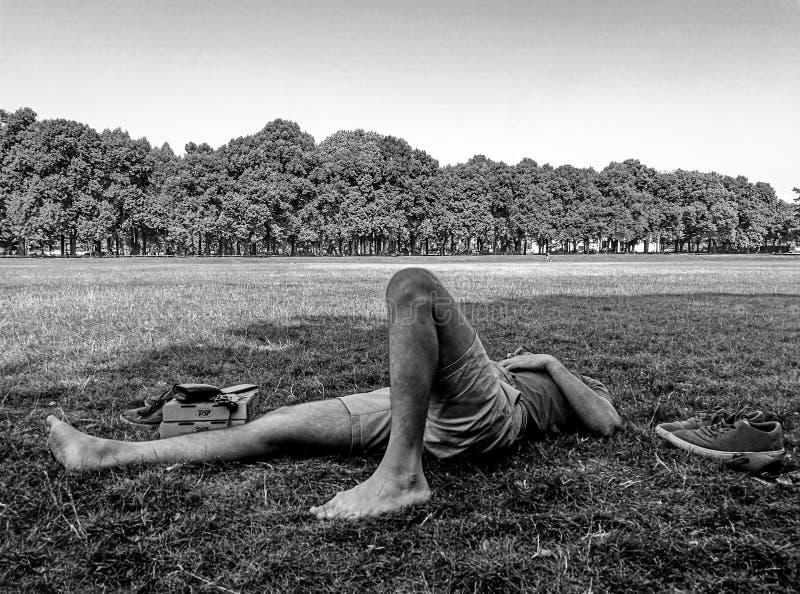Den unga manliga skateboradåkaren som vilar på gräset med hans ögon, stängde sig arkivfoto