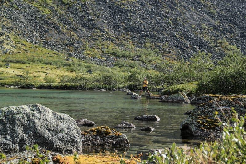 Den unga manliga turisten fotograferar en härlig genomskinlig sjö med dolda stenar för mossa royaltyfri foto